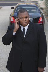 Chauffeur stands on mobile phone with luxury vehicle
