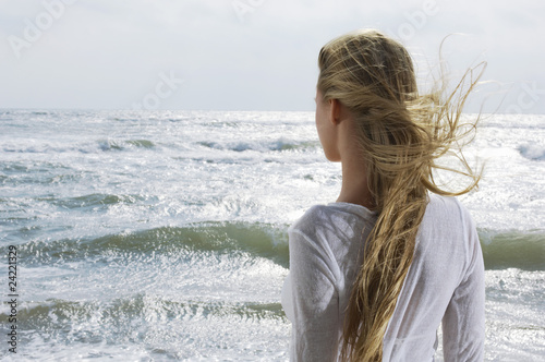 Young woman looking at ocean, back view