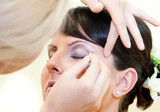 beautician applying make up to young woman poster