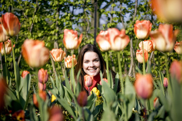 A young woman sitting amongst tulips, smiling