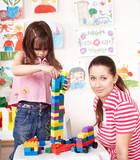 Child playing  lego constraction with mother. poster