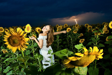 Woman inside sunflowers field over clody lightning sky