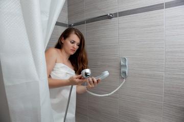 gorgeous woman behind curtain making a call at modern bathroom