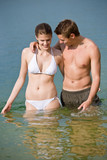 Couple in swimwear enjoy water and sun in summer poster