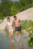 Couple in swimwear jogging at lakeside poster