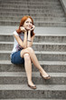 Portrait of beautiful red-haired girl on footstep.