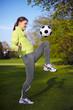 Frau jongliert Fußball auf dem Knie