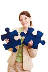 Geschäftsfrau mit zwei Puzzleteilen
