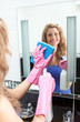 Smiling woman cleaning a mirror
