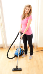 Smiling woman use vacuum cleaner
