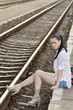 pretty young lady sitting on platform and waiting the train