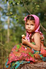 Девочка в пестром сарафане сидит на пеньке