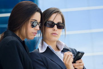 two businesswomen working referring to a mobile phone