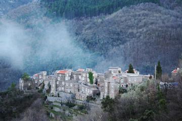 piccolo villaggio con una nuvola bassa sulla cima di una collina