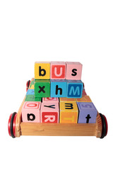 childrens play blocks spelling bus in wooden cart isolated on wh