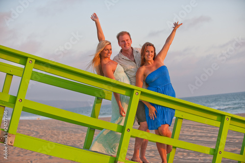 two beautiful women and man on California beach coast