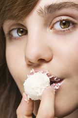 Woman biting white candy
