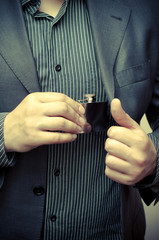 man taking a flask out of his suit pocket
