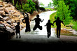 Young Children Playing and Jumping in Sillouette in Rain