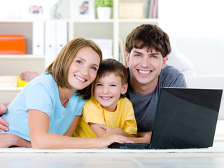 Happy family with son at home with laptop