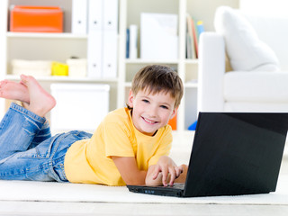 Little boy with laptop lying down at home