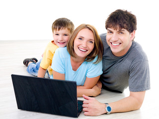 Three laughing people with one laptop