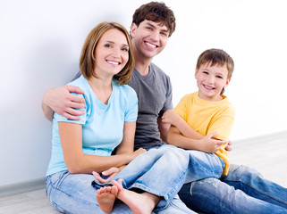 Happy family in casuals sitting on the floor
