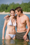 Couple in swimwear enjoy water and sun poster