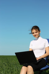 Business woman on a laptop in a field out side the office
