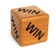 Wooden dice with the word WIN on it over white background