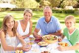 Family Enjoying Meal In Garden