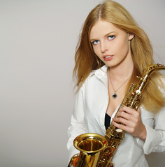 Portrait of pretty blonde woman with a shiny saxophone
