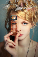 beautiful girl with a bottle of perfume about her face
