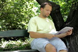 Man sitting in the park and reading newspaper