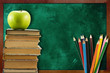 books with apple and pencils against blackboard