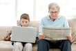 Old man reading newspaper with his grand son using laptop