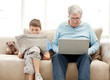 Old man using a laptop with his grand son reading a newspaper