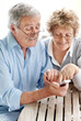 Happy old couple using a mobile phone