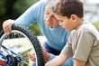 Little boy and his grand father rapairing a cycle