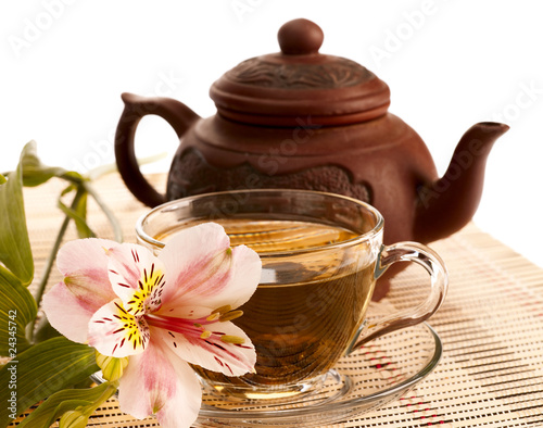 Cup of green tea on the table with orchid flower