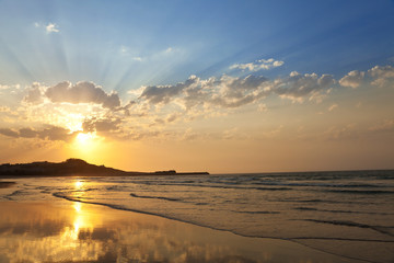 Nice sunset with lots of sunbeams at a lonely beach