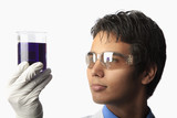 lab technician holding a beaker with fluid inside poster