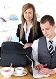 Businesswoman packing her bag businessman using laptop
