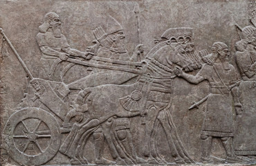 Relief of ancient assyrian warriors in a horse drawn chariot