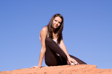 Girl sitting on red rocks