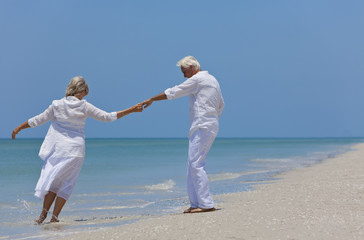 Happy Senior Couple Dancing Holding Hands on A Tropical Beach