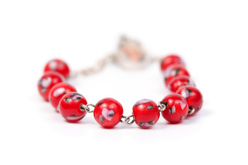 Bracelet with red beads isolated on white background