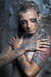 Naked tattooed woman with face and body painted with black paint