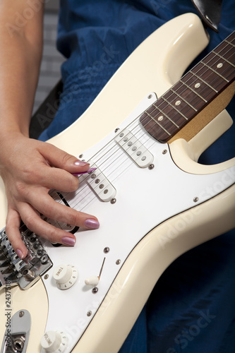 Young woman playing white electric guitar
