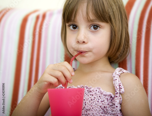 Child drinking juice sitting on her bed at home